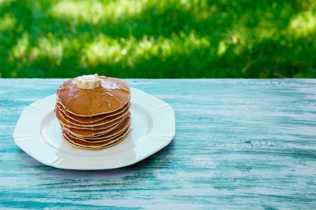 Panqueques con mantequilla y miel en plato blanco en jardín de madera azul o en la naturaleza. pila de panqueques de oro o torta de panqueques, primer de oro.