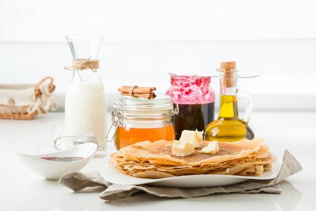 Panqueques con mantequilla sobre un fondo blanco