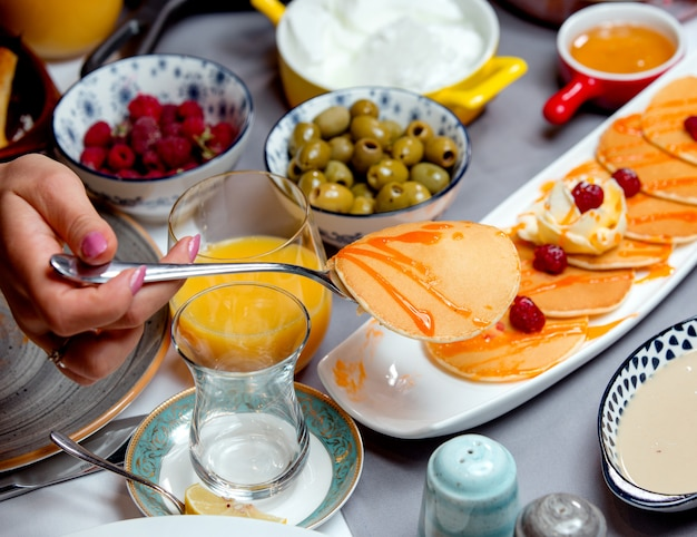Panqueques con mermelada, aceitunas, un vaso de jugo y frambuesas