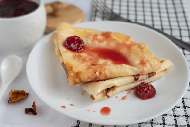 Panqueques con mermelada de bayas y bayas en una placa blanca.