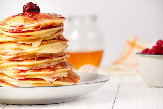 Panqueques con mermelada de cerezas en mesa