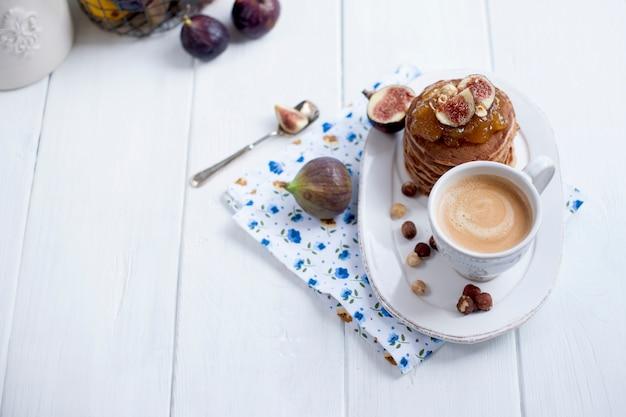 Panqueques con mermelada e higos en un plato blanco y una taza de café sobre un fondo blanco.