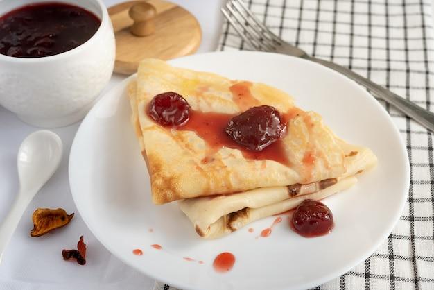 Panqueques con mermelada de fresa en una placa blanca.