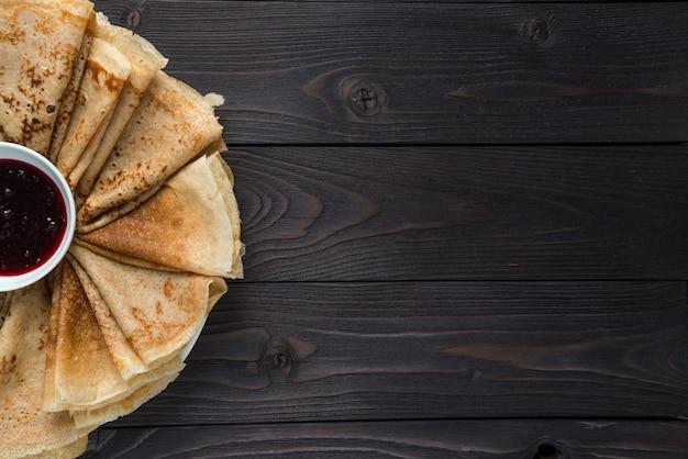 Panqueques con mermelada sobre un fondo de madera