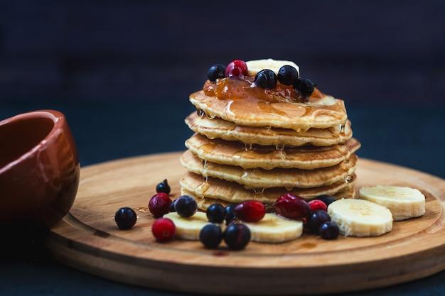 Panqueques con miel, plátanos, mermelada y bayas en un plato de madera menú, receta de restaurante. servido en