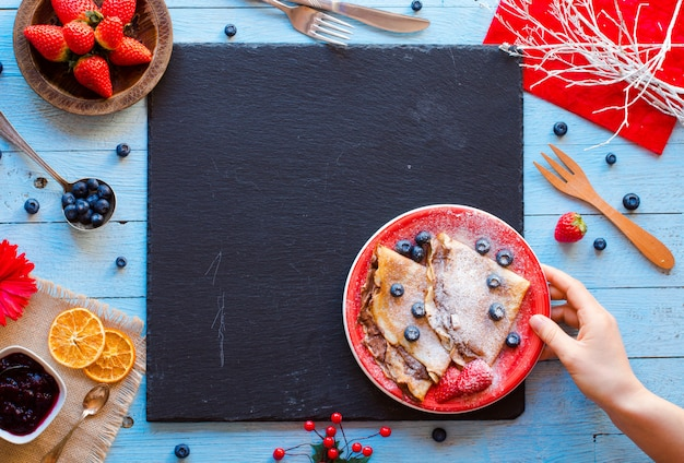 Panqueques o crepes de fresas frescas con bayas y chocolate