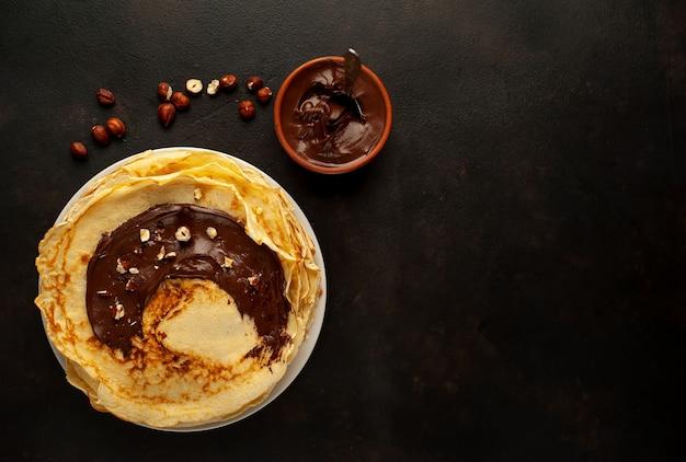 Panqueques con pasta de chocolate y avellanas, en un plato blanco sobre un fondo de hormigón, pizarra con espacio de copia para su texto