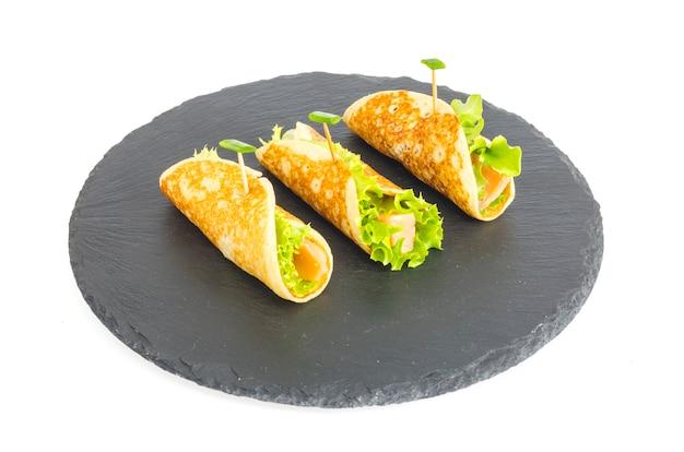 Panqueques con pescado y lechuga. rollo de pan de salmón con queso. sobre placa de piedra negra.