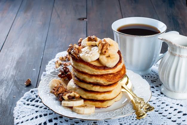 Panqueques con plátano, nueces, miel y taza de café oscuro