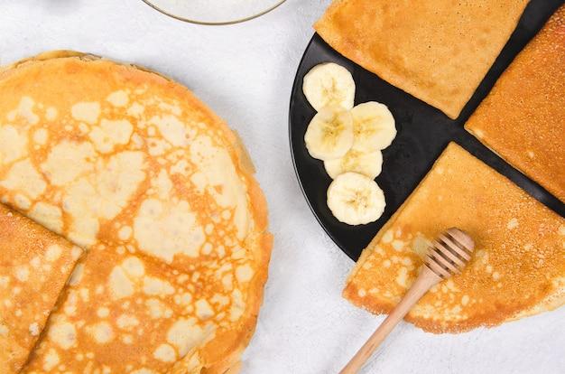 Panqueques con plátanos para el desayuno en la mesa blanca