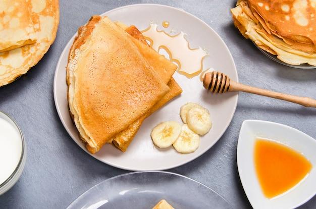 Panqueques con plátanos y miel para el desayuno en la mesa blanca