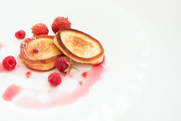 Panqueques en el plato blanco con mermelada de frambuesa