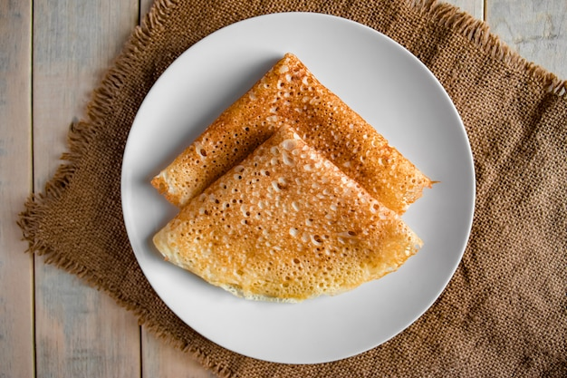 Panqueques en un plato blanco sobre un fondo de lino. crepes de comida tradicional rusa para la fiesta maslenitsa.