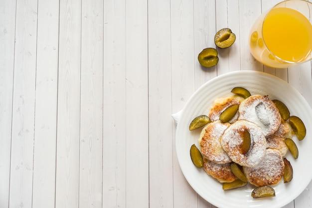 Panqueques de queso en azúcar en polvo con ciruelas frescas en un plato
