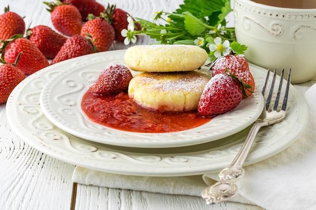Panqueques de queso con bayas y azúcar en polvo, flores, desayuno saludable