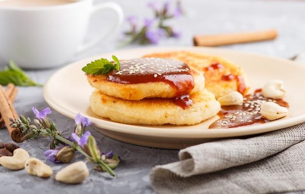 Panqueques de queso con salsa de caramelo en un plato de cerámica color beige y una taza de café en concreto gris
