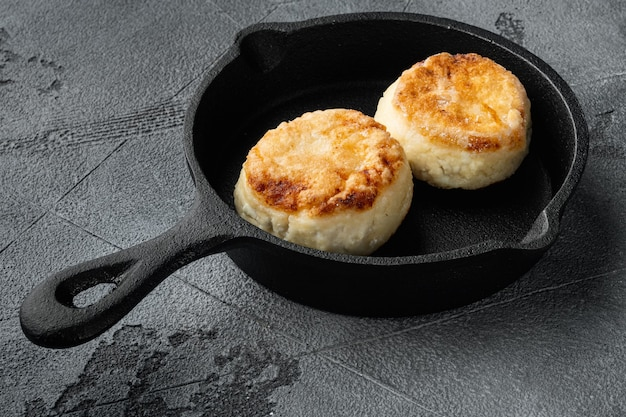 Panqueques de queso en sartén sartén de hierro fundido en sartén sartén de hierro fundido, sobre fondo de tabla de piedra gris