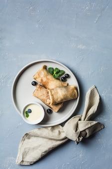 Unos panqueques con relleno en una placa gris con arándanos y menta, con leche dulce condensada en una salsera sobre un fondo azul claro.