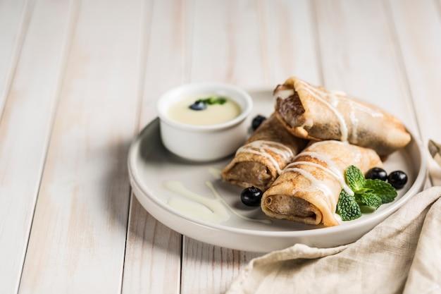 Unos panqueques con relleno en un plato gris con arándanos y menta, con leche dulce condensada en una salsera