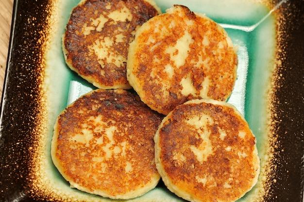 Panqueques de requesón recién horneados con crema agria en un plato