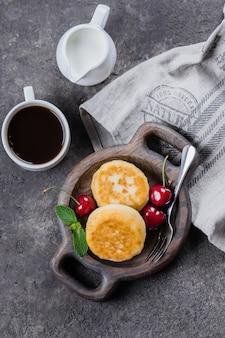 Panqueques de requesón, syrniki, buñuelos de cuajada con cereza