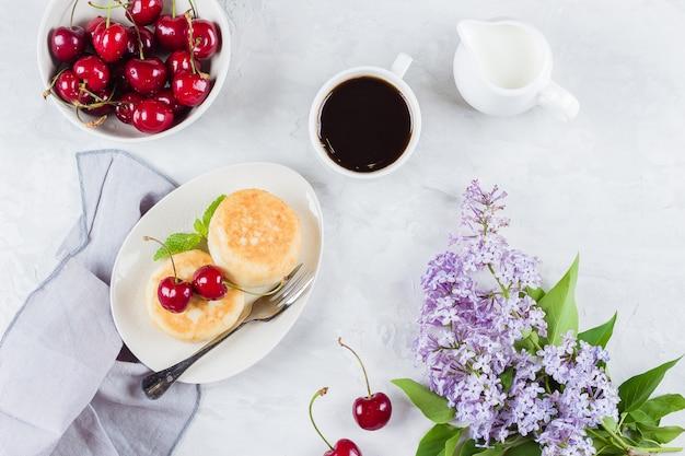 Panqueques de requesón, taza de café negro, leche y tazón.