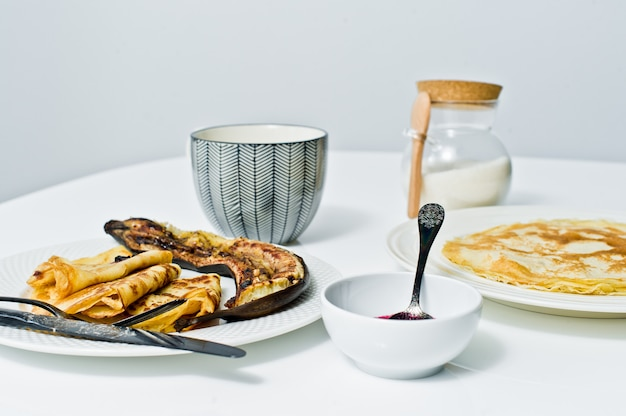 Panqueques rusos tradicionales con mermelada de arándanos, desayuno con café.