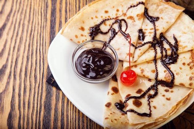 Panqueques con salsa de chocolate en mesa de madera