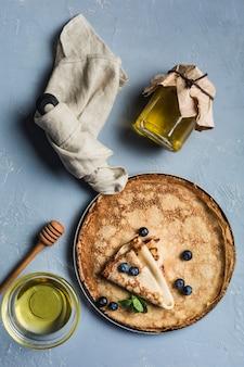 Unos panqueques en una sartén con arándanos y menta, con un tarro de miel y una cuchara de madera.