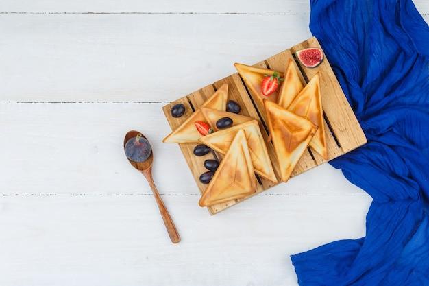 Panqueques sobre tabla de madera con cuchara de madera y frutas
