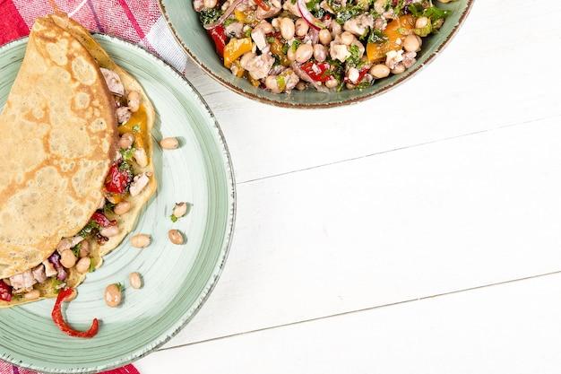 Panqueques de trigo sarraceno salados con frijoles blancos, pimiento rojo y amarillo, perejil y pollo