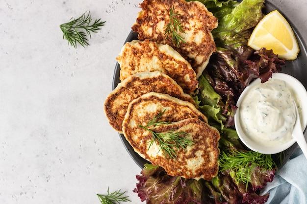 Panqueques de vegetales (coliflor) (buñuelos) con aderezo de yogurt natural y eneldo.