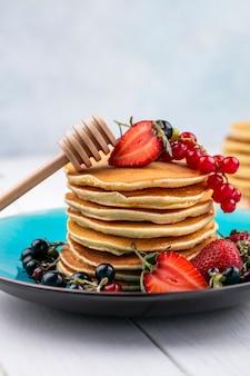 Panqueques de vista frontal con fresas grosellas negras y rojas en un plato con un palo para miel
