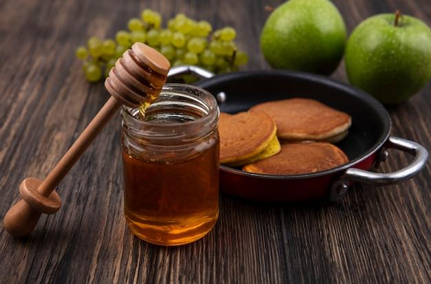 Panqueques de vista frontal en una sartén con miel en un frasco con una cuchara de madera y uvas verdes con manzanas sobre un fondo de madera