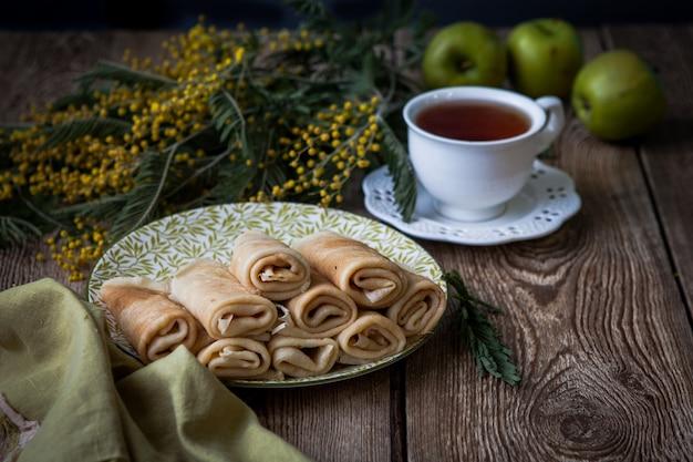 Panqueques de vista lateral con taza de té y flores de mimosa y manzana en mesa de madera