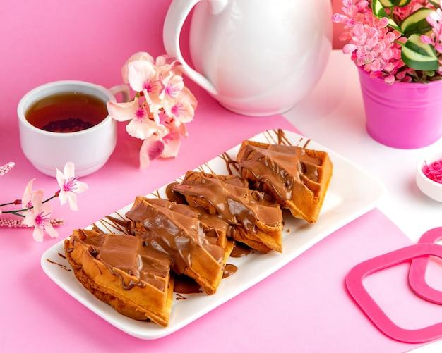 Panqueques waffle panqueques con chocolate y té negro en la mesa