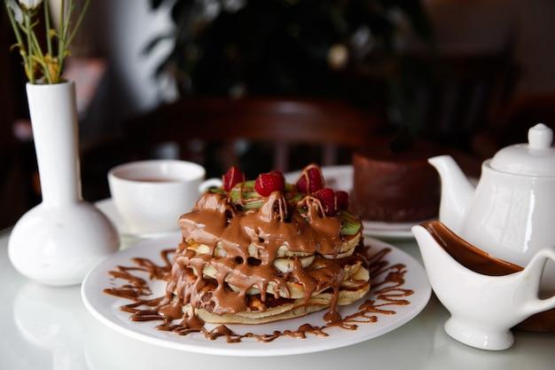 Panqueques de waffle de vista frontal con plátanos, kiwi y fresas con chocolate vertido encima en un plato