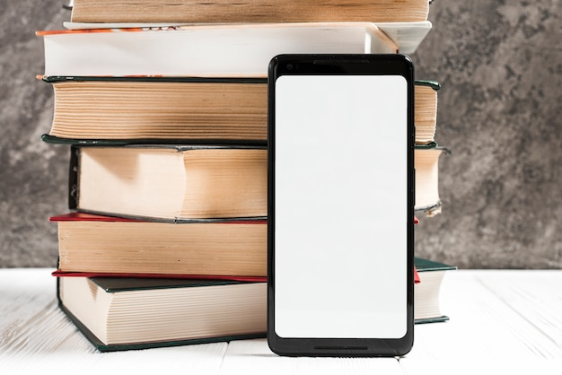 Pantalla blanca en blanco con teléfono móvil frente al libro apilado en la mesa