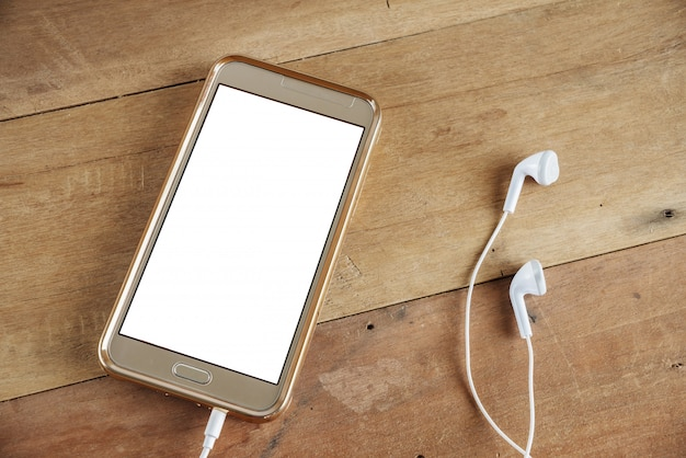 Pantalla blanca móvil del teléfono aislada en la superficie de la mesa de madera