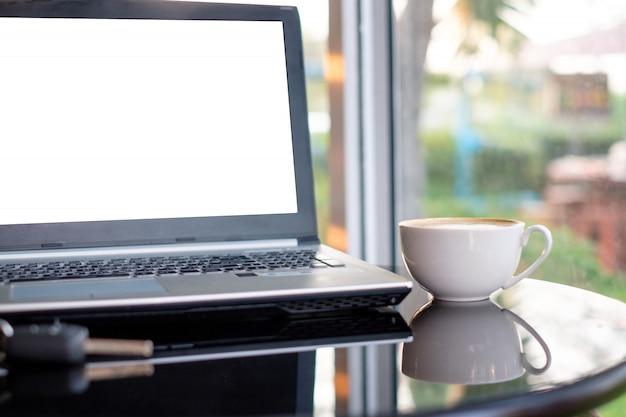Pantalla blanca portátil con taza de café en mesa de cristal