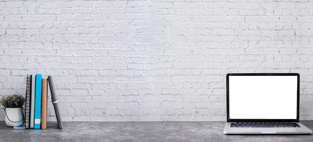 Pantalla en blanco en la computadora portátil con libros y cuadernos de papel sobre fondo de textura de pared de ladrillo.