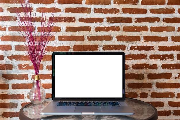 Pantalla en blanco de la computadora portátil en la mesa con pared de ladrillo rojo