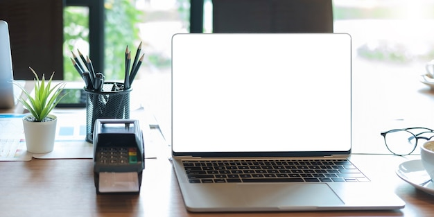 Pantalla en blanco del portátil con máquina edc en una mesa en una cafetería.