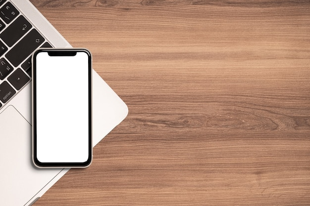 Pantalla en blanco de smartphone y computadora portátil para maqueta sobre fondo de escritorio de madera hermosa.
