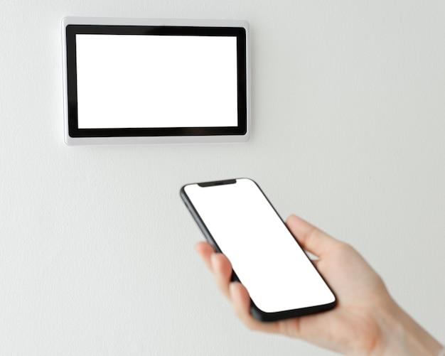 Pantalla en blanco del teléfono con monitor de panel de automatización del hogar inteligente en blanco