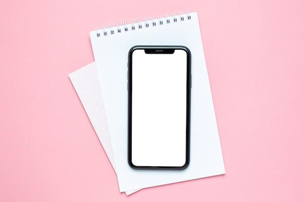 Pantalla en blanco del teléfono móvil y cuaderno del negocio en rosa. escritorio de trabajo de la mujer.