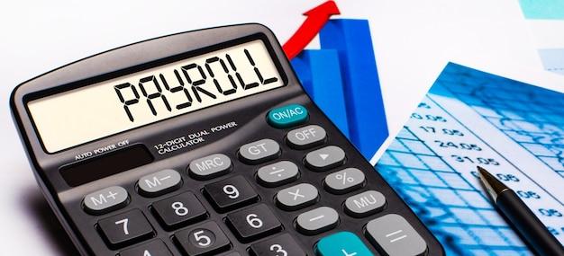 En la pantalla de la calculadora hay una inscripción payroll. cerca hay diagramas y gráficos de colores. concepto de negocio