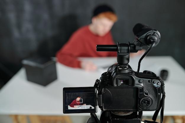 Pantalla de cámara de vídeo delante del joven vlogger sentado en el escritorio contra el fondo negro en el estudio