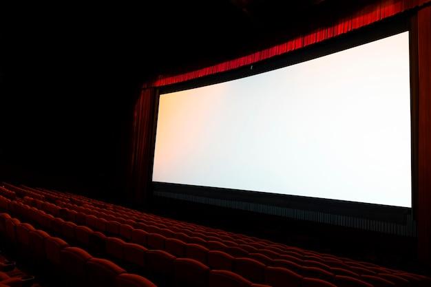 Pantalla de cine con asientos rojos abiertos