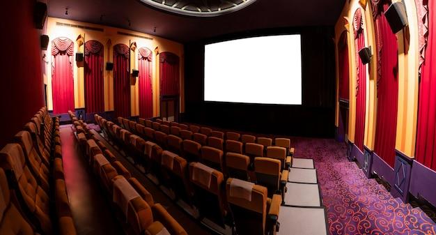 Pantalla de cine delante de las filas de asientos en el cine que muestra la pantalla en blanco proyectada desde el cinematógrafo